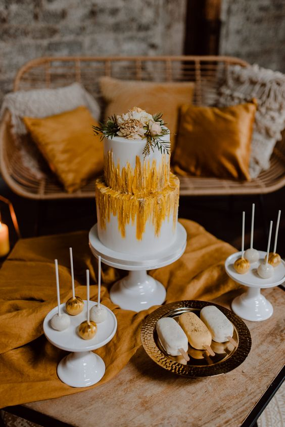 a boho wedding cake with yellow and rust textural patterns and neutral blooms and greenery on top