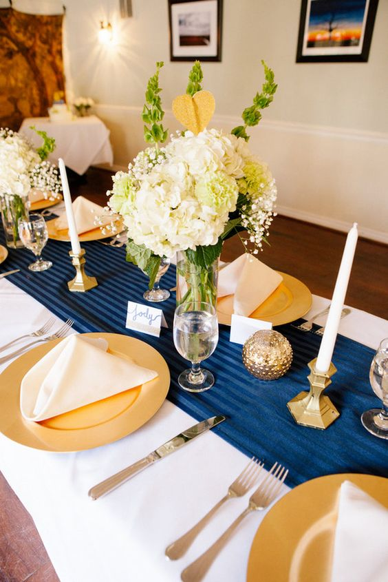 a bold navy, gold and creamy tablescape with gold chargers, balls and neutral blooms