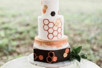 a bold white, black and copper wedding cake with watercolors and hexagons all over the cake plus greenery and blooms is a lovely idea