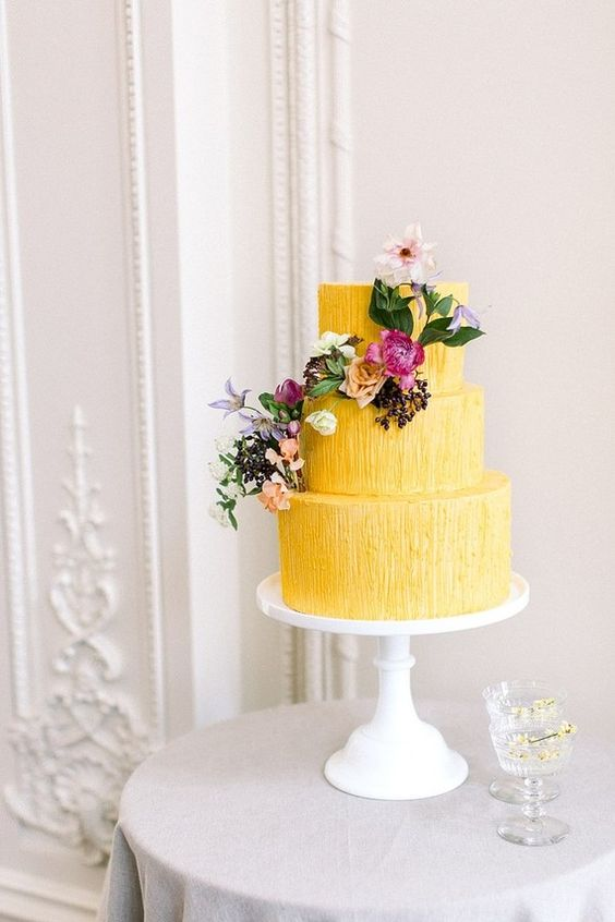 a bold yellow textural wedding cake with bold blooms, greenery and pastel touches is a refined and chic idea