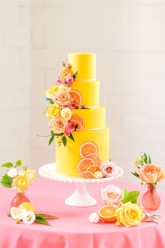 a bold yellow wedding cake with peachy and yellow blooms, greenery and dried citrus attached