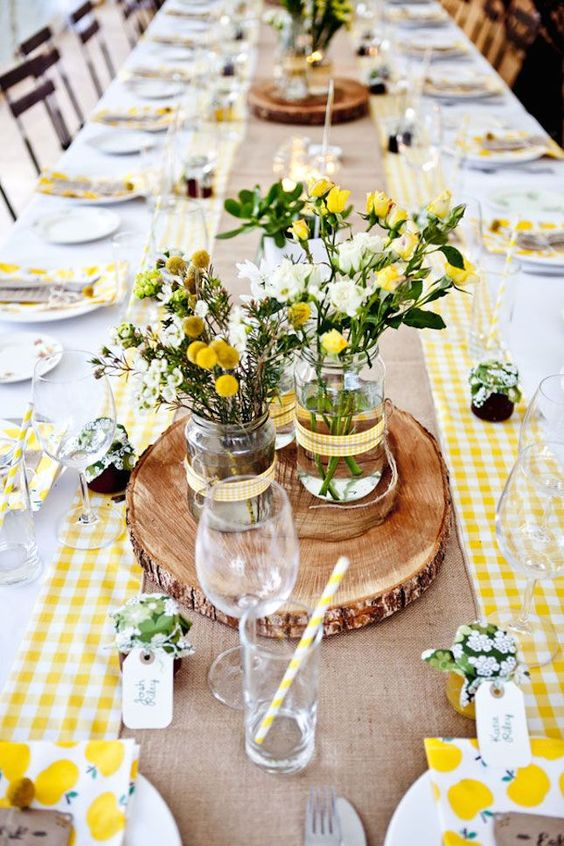 a bright barn wedding table with a burlap runner, bright yellow plaids, a wood slice, printed napkins and jam favors