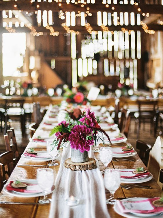 a bright barn wedding table with a white runner, a bright floral centerpiece, fuchsia napkins, white porcelain