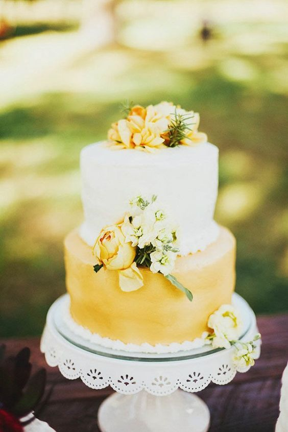 a bright wedding cake with a white and yellow tier, with peachy and white blooms and greenery is super cool