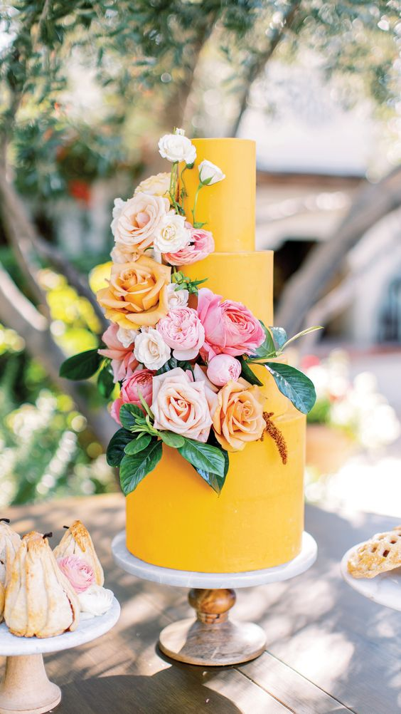 a bright yellow wedding cake with blush, peachy, pink and white blooms and leaves is a cool and fun idea to rock