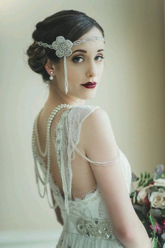 a catchy embellished bridal headband, an embellished flower and hanging pearls for a unique bridal look