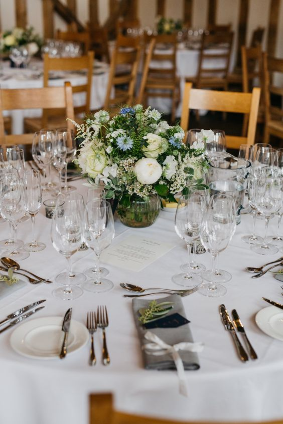 a chic barn wedding table with neutral linens, a white and blue flower centerpiece and neutral stationery