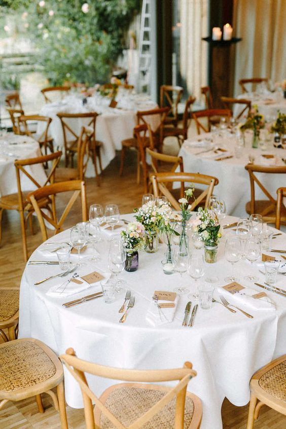 a chic barn wedding table with white linens, wildflowers in jars, candles and tags and cards