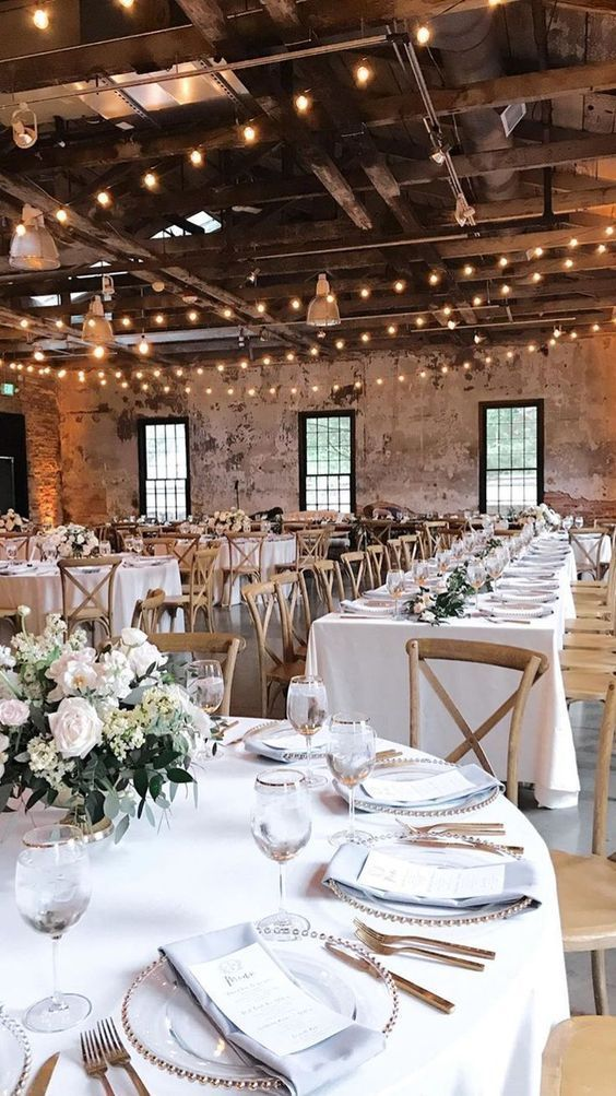 a chic barn wedding tablescape with white linens, white blooms and greenery and silver cutlery and chargers
