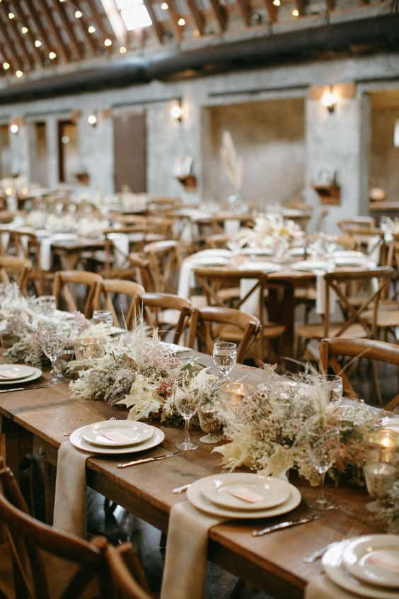 a chic barn wedidng table with a long dried foliage and blooms table runner, neutral linens and porcelain