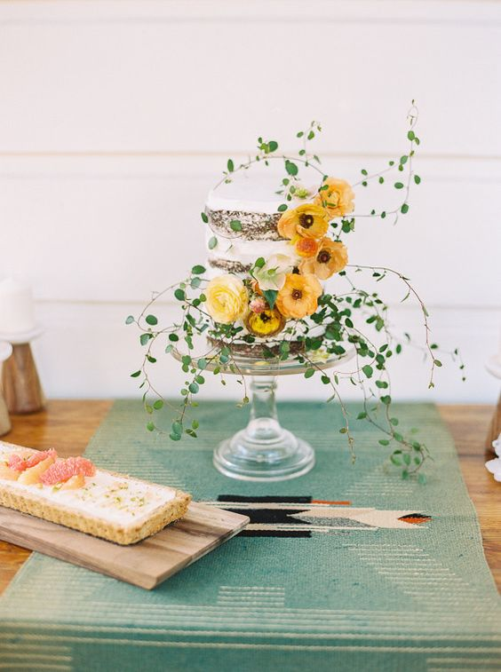 a chic naked wedding cake with lush greenery and yellow blooms is a beautiful ethereal wedding dessert for spring or summer