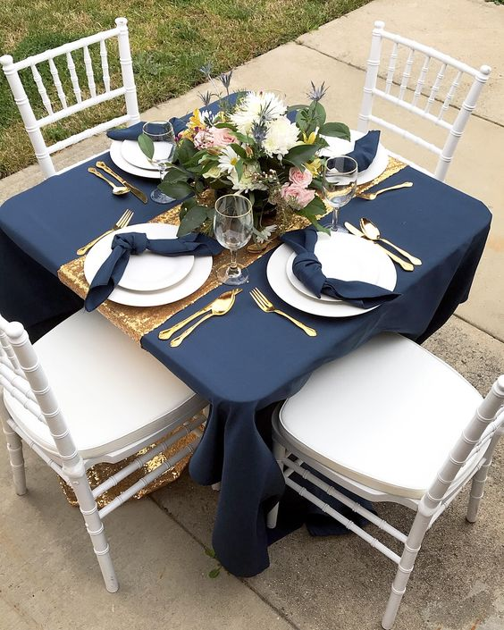 a chic navy and gold table setting with white plates and chargers, gold cutlery and a neutral floral centerpiece