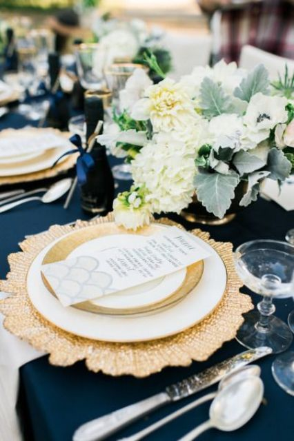 a chic navy, gold and creamy wedding tablescape with lush floral centerpieces