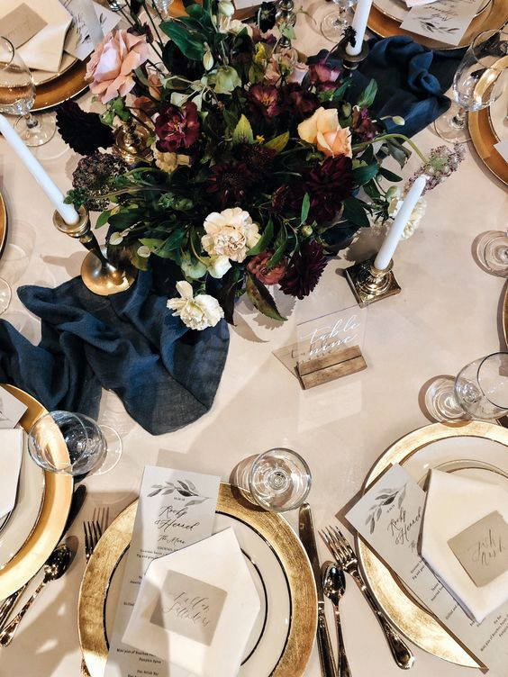 a chic tablescape with much gold, a navy table runner, a moody floral centerpiece and candles