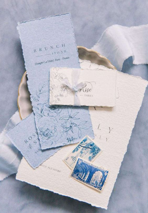 a chic wedding invitation suite in white and powder blue, with a rough edge and cool letters