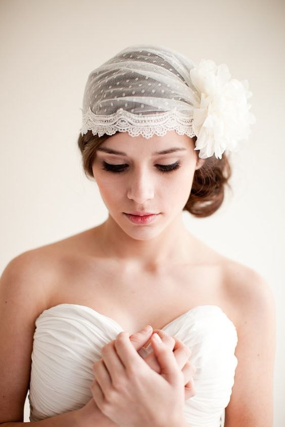a classic Juliet cap veil of lace, with a large white fabric bloom is a pretty idea for a vintage or art deco bride