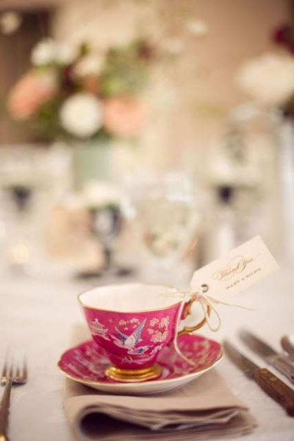 a colorful vintage teacup with an escort card is a lovely wedding favor idea that is budget friendly