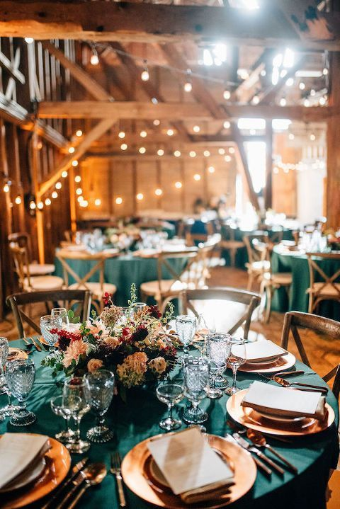 a colorful wedding tablescape with a lush floral centerpiece, copper chargers, cool glasses and a teal tablecloth