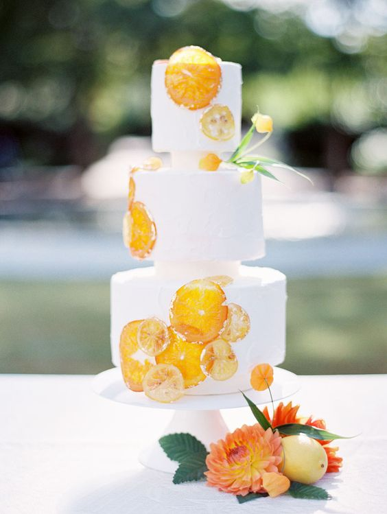 a creative white wedding cake with dried citrus slices and some blooms is a cool and bold wedding dessert