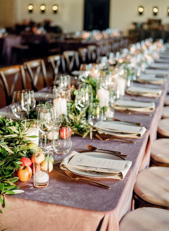 a fall barn wedding tablescape with a mauve tablecloth, greenery, apples and pillar candles