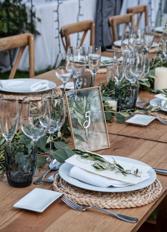 a fresh barn wedding tablescape with an uncovered table, a woven placemat, greenery and a framed table number