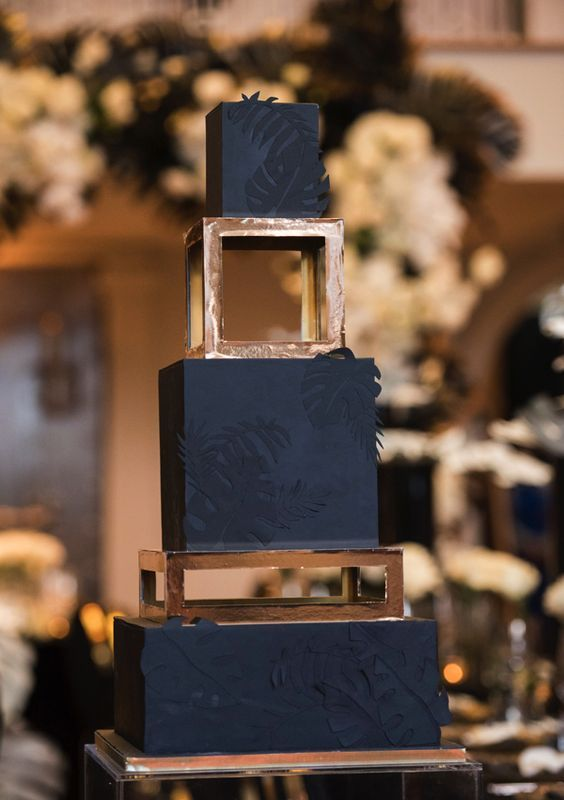 a glam tropical wedding cake with graphite grey and copper tiers, the grey tiers are decorated with black tropical leaves and copper stands add glam