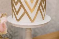 a gold and white one-tier geometric wedding cake is a super stylish and bold idea to rock at a modern wedding