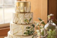 a gold and white wedding cake decorated with shards and with painted greenery and blooms is a stylish and lovely idea