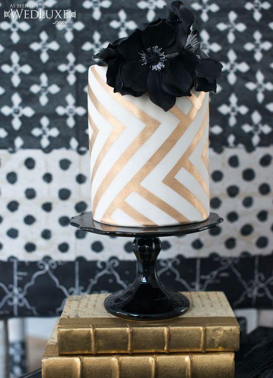 a cute gold white wedding cake with geometric decor