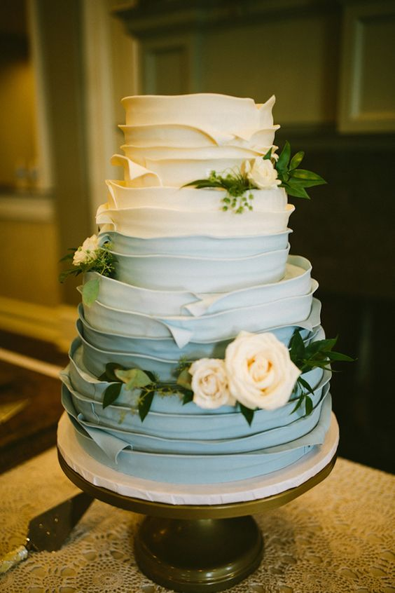 a gorgeous ombre textural powder blue wedding cake decorated with neutral blooms and greenery