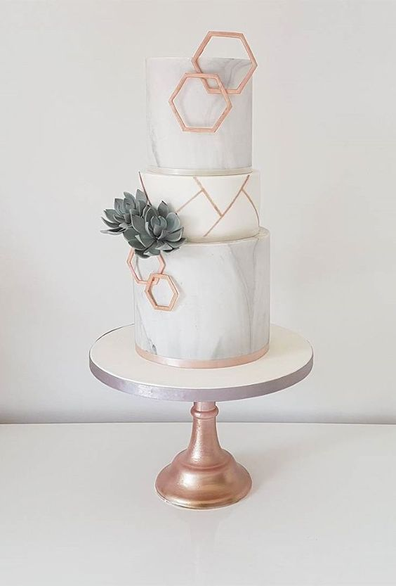 a grey marble and white wedding cake with sugar succulents, copper hexagons and shards is a stylish idea for a modern wedding