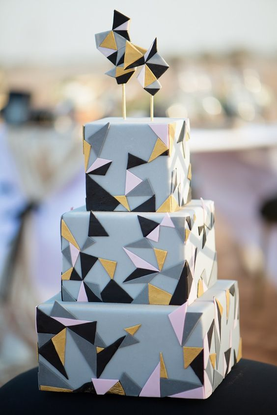 a grey square wedding cake with pink, gold, grey and black triangles and matching geometric toppers looks very fun and very eye-catchy