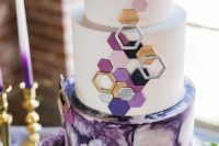 a jaw-dropping round wedding cake with a purple watercolor and white tiers, with 3D hexagons covering the tiers is just fantastic