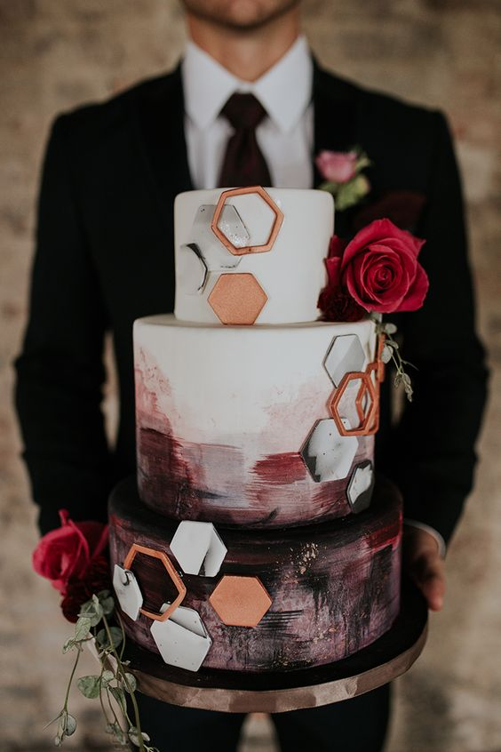 a jaw dropping wedding cake with burgundy and black brushstrokes, white and copper hexagons and pink roses plus greenery