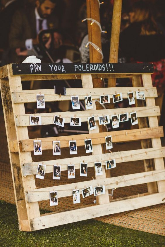 a large chalkboard pallet with Polaroids attached is a cool rustic wedding guest book idea