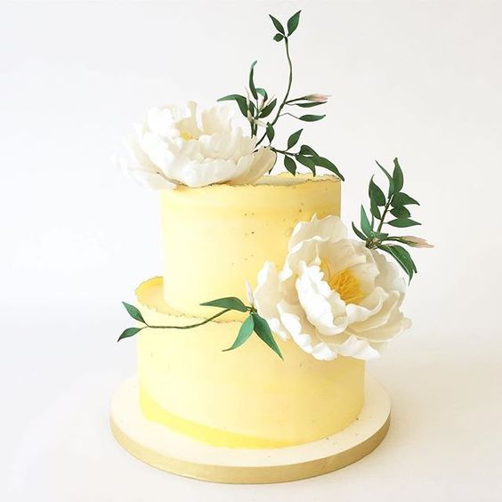 a light yellow wedding cake with an uneven edge, white blooms and greenery is a cool and fun idea for spring