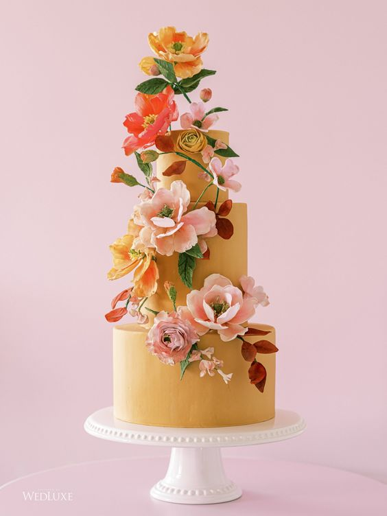 a mustard wedding cake with bright blooms, greenery is a refined and elegant wedding dessert idea