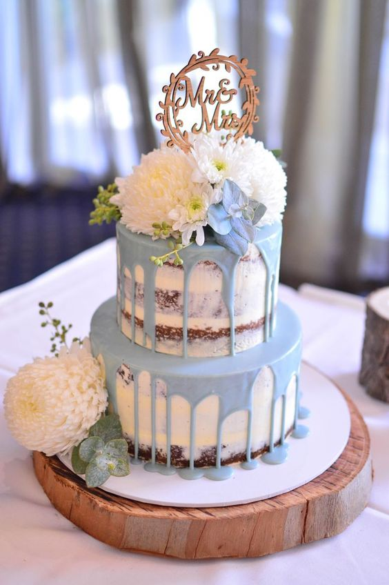 a naked wedding cake with powder blue drip, blue and white blooms and a wooden topper