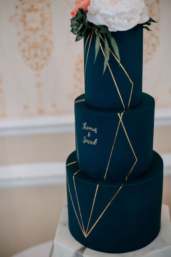 a navy and gold wedding cake with calligraphy and fresh blooms on top looks very chic
