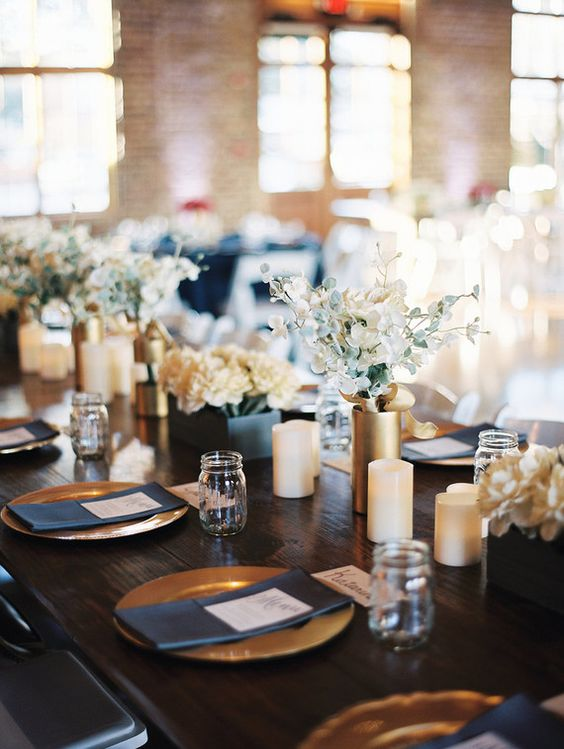 a navy and gold wedding table setting with white and gold candles, neutral blooms and gold chargers