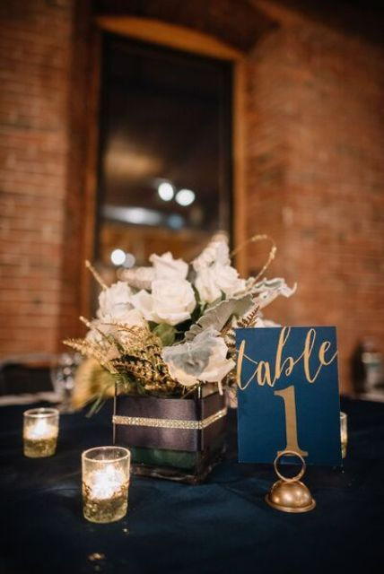 a navy and gold wedding tablescape with candle holders, table numbers and a white bloom centerpiece