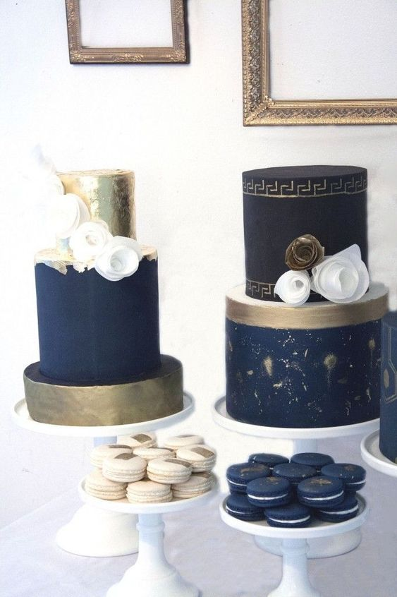 a navy, gold and creamy wedding dessert table with macarons and cakes