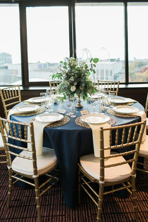 a navy, gold and creamy wedding tablescape with a lush greenery and neutral bloom centerpiece