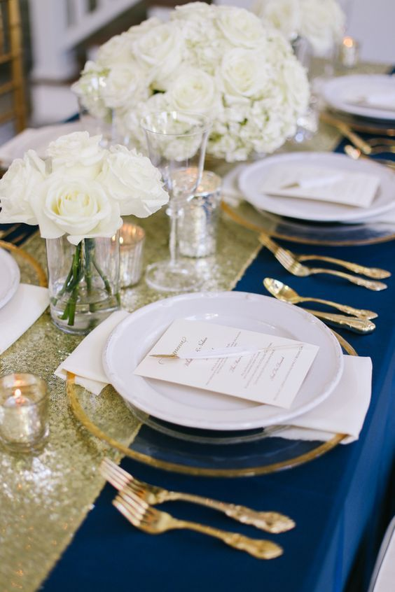 a navy, gold glitter and creamy tablescape plus gold cutlery and candle holders