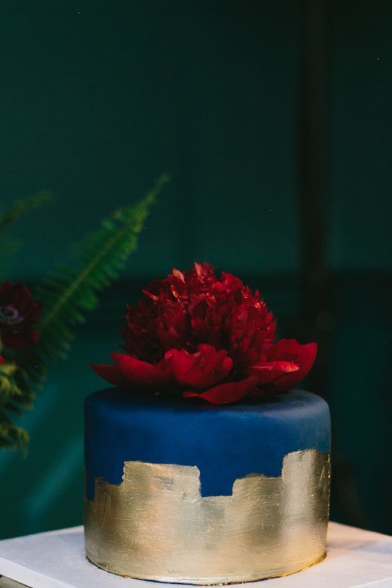 a navy wedding cake decorated with gold leaf and a large burgundy bloom on top