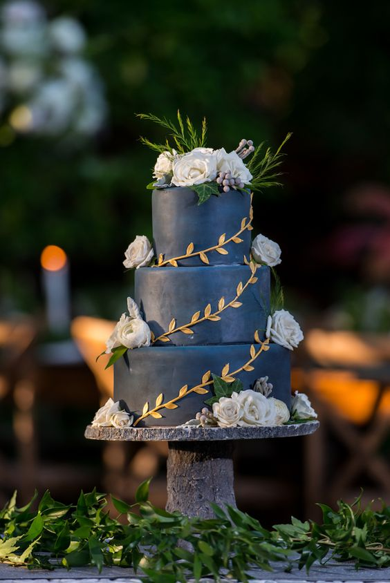 a navy wedding cake decorated with gold leaves, white blooms and berries