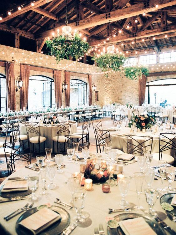 a neutral barn wedding table setting with silver chargers, neutral linens, a peachy terrarium centerpieces and votives