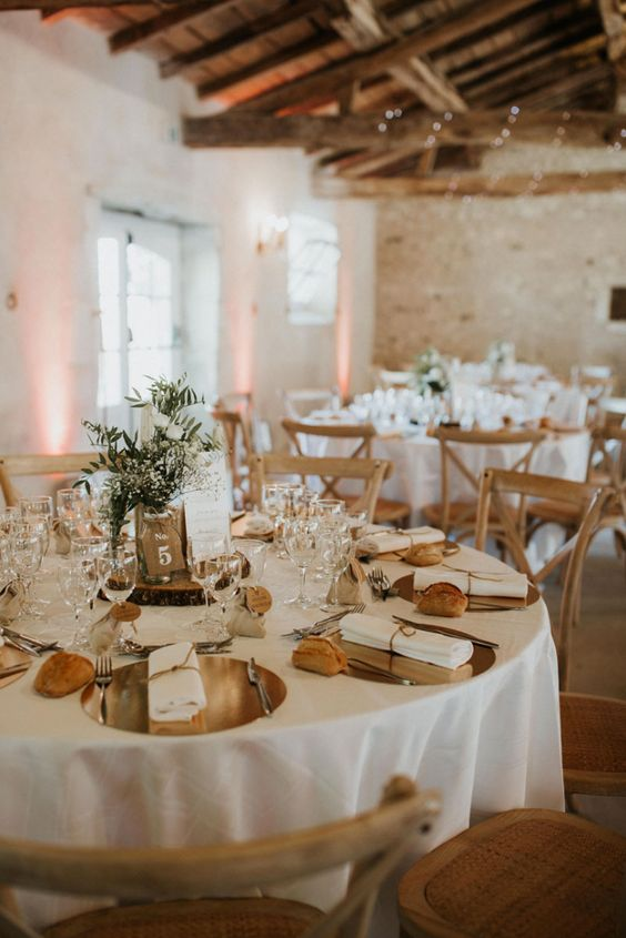 a neutral barn wedding table with shiny chargers, a greenery centerpiece on a wood slice, some candles and bread