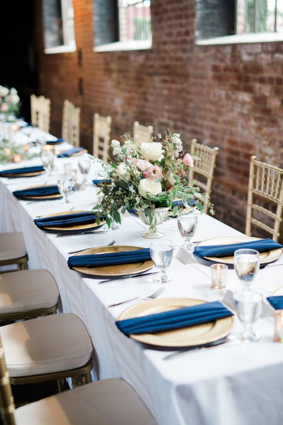 a neutral table setting with gold chargers, navy napkins and a cute neutral floral centerpiece