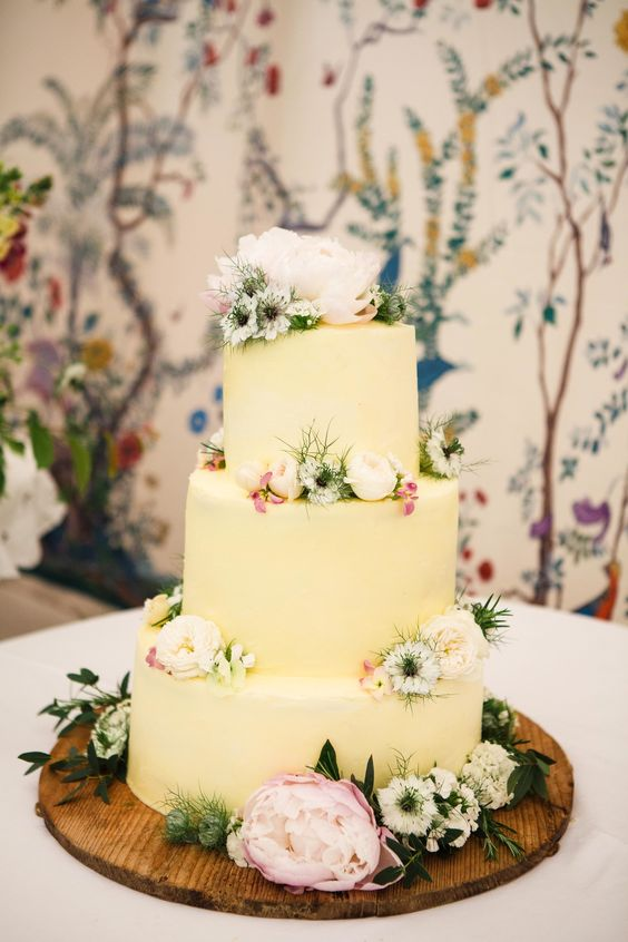 a pale yellow wedding cake with greenery, white and blush blooms is a beautiful and cool idea for spring